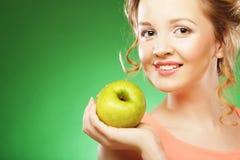 白肤金发的妇女吃在绿色背景的绿色苹果 免版税库存图片
