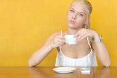 白肤金发的妇女喝咖啡在咖啡馆 免版税库存图片