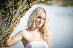 白肤金发的妇女在树下 免版税库存图片