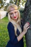 年轻白肤金发的妇女在树附近的公园 库存图片