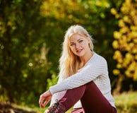 白肤金发的妇女在秋天庭院里 库存照片