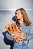 白肤金发的妇女在他们的手上拿着与新鲜的法国长方形宝石的一个纸袋 库存图片