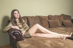 白肤金发的妇女坐一个长沙发在房子里 免版税库存图片