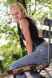 白肤金发的妇女坐一条长凳在公园 免版税库存照片