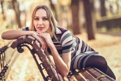 年轻白肤金发的妇女坐公园的长凳 图库摄影