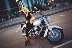 年轻白肤金发的妇女坐在背景的一辆摩托车  免版税图库摄影