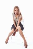 年轻白肤金发的妇女坐在裙子的一把椅子 免版税库存图片