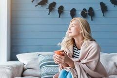 白肤金发的妇女坐有杯子的沙发 免版税库存图片