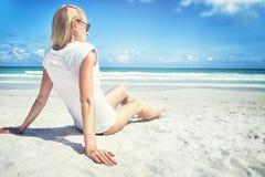 年轻白肤金发的妇女坐海滩 库存图片