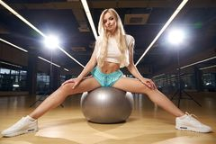 白肤金发的妇女坐瑞士球 免版税库存图片