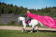 白肤金发的妇女坐马 免版税库存照片