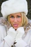 白肤金发的妇女女孩白色裘皮帽,伸出她的舌头的外套 免版税图库摄影