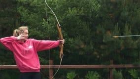 白肤金发的妇女射击弓箭 股票录像