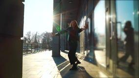 白肤金发的妇女执行的当代舞蹈在日落光芒在城市街道上的 影视素材