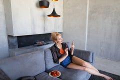 白肤金发的妇女拿着手机并且吃成熟草莓,坐 库存图片