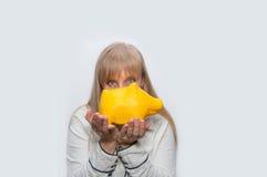 白肤金发的妇女显示黄色猪monebox 免版税库存照片