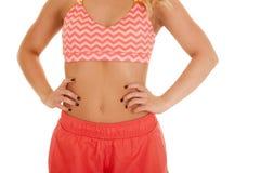 白肤金发的妇女橙色短裤体育胸罩关闭递胃 库存照片