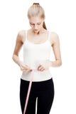 年轻白肤金发的妇女测量的腰部 库存图片