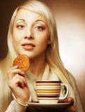 白肤金发的妇女用咖啡和曲奇饼 免版税图库摄影