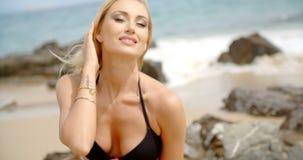白肤金发的妇女用在头发的手在多岩石的海滩 股票录像