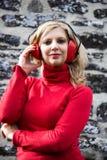 白肤金发的妇女画象有红色御寒耳罩的在石墙backgrou 库存图片