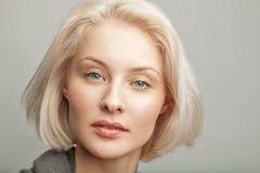 年轻白肤金发的妇女艺术性的画象灰色背景的 免版税图库摄影