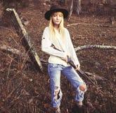 年轻白肤金发的妇女选址在有枪的森林 免版税图库摄影