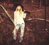 年轻白肤金发的妇女选址在有枪的森林 免版税库存照片