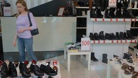 白肤金发的妇女选择在鞋子精品店的鞋子 股票录像