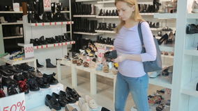 白肤金发的妇女选择在鞋子精品店的鞋子 股票视频