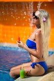 白肤金发的妇女长的头发在水池附近吃西瓜 免版税库存图片