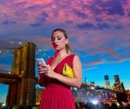 白肤金发的妇女闲谈文字智能手机在布鲁克林 免版税库存照片