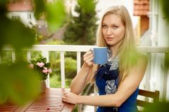 年轻白肤金发的妇女饮用的茶画象  免版税库存照片