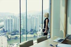 白肤金发的妇女骄傲的CEO在与都市风景的办公室窗口拿着触摸板并且看 免版税库存照片