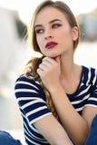 白肤金发的妇女,时尚模型,坐在都市背景中 免版税库存图片