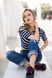 白肤金发的妇女,时尚模型,坐在都市背景中 库存图片