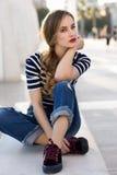 白肤金发的妇女,时尚模型,坐在都市背景中 库存照片