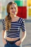 白肤金发的妇女,时尚模型,微笑在都市背景中 免版税库存照片