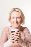 白肤金发的妇女直接地注视,当拿着一纸杯时 图库摄影