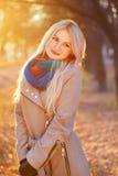 白肤金发的妇女画象在有阳光的秋天公园 免版税库存图片
