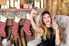年轻白肤金发的妇女画象有香槟做selfie的一杯的 免版税库存图片