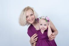 白肤金发的妈妈和女儿在白色背景的演播室 图库摄影