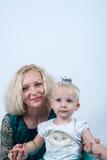 白肤金发的妈妈和女儿在白色背景的演播室 免版税图库摄影