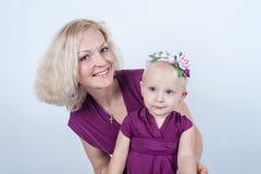 白肤金发的妈妈和女儿在白色背景的演播室 库存照片