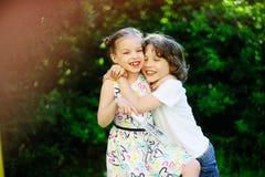 白肤金发的嬉戏地拥抱男孩和的女孩 免版税库存照片