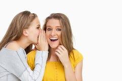 白肤金发的学员耳语对朋友 库存照片