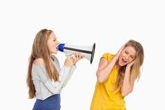 白肤金发的学生叫喊与在其他女孩的一台扩音器 图库摄影