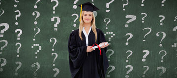 白肤金发的学生的综合图象拿着她的文凭的毕业生长袍的 库存照片