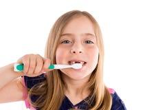 白肤金发的孩子凹进的女孩清洁牙牙刷 免版税库存图片