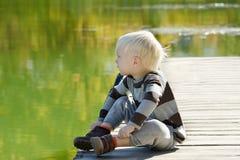 白肤金发的孩子坐船坞 秋天,一个晴天 河禁令 免版税库存照片